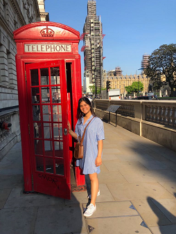 A picture of Alejandra standing in the sunshine beside one of London's famous red telephone boxes.